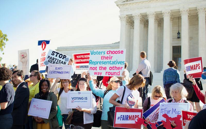 Rally participants stand in front of the Supreme Court with signs demanding fair maps