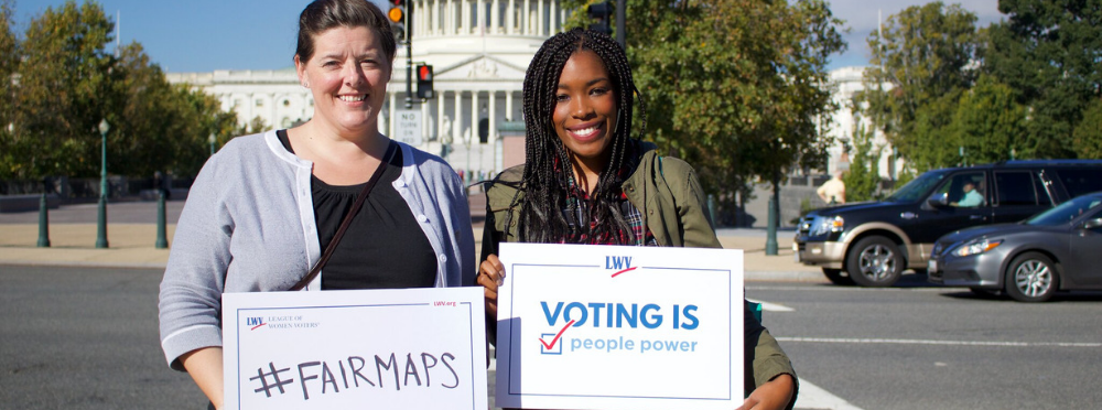 Two women holding #Fairmaps signs in front of Capitol
